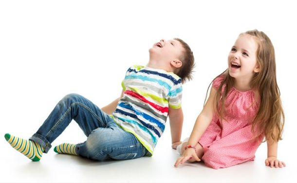 a little boy and a littler girl laughing sitting on the floor