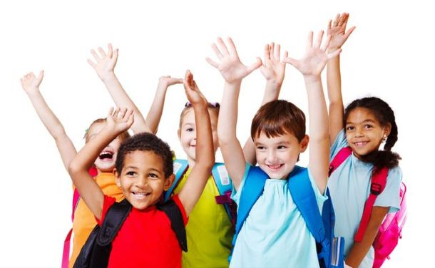 group of multi-ethnic kids smiling with their hands up and carrying satchels